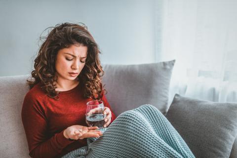 Una mujer consumiendo pastillas.