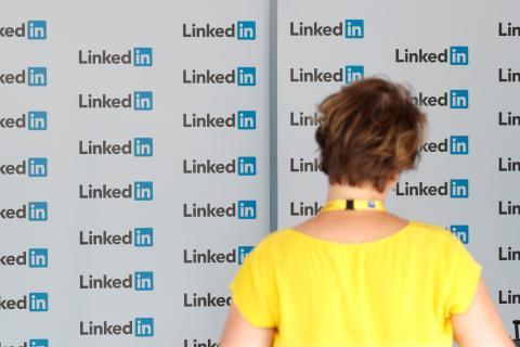 Una mujer delante de una pared con el logo de LinkedIn