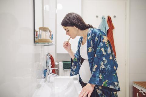 Mujer embarazada se lava los dientes.