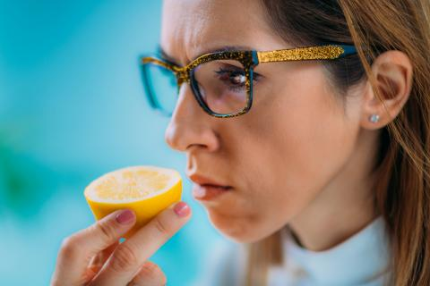 Mujer huele un limón.