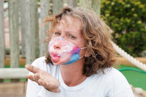 Mujer con mascarilla lanza un beso.