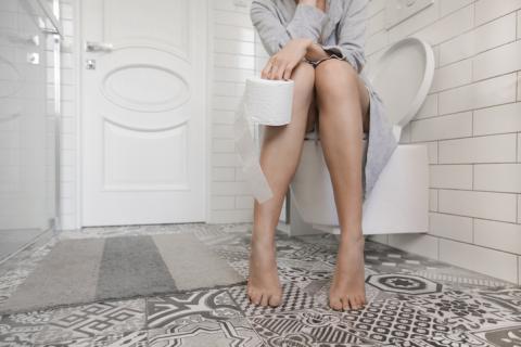 Mujer sentada en el váter.