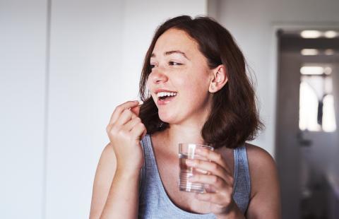 mujer tomando pastilla, suplementos