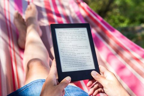 Mujer tumbada en una amaca leyendo Kindle