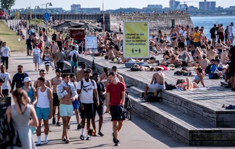 Una multitud de gente sin mascarilla en Malmo, Suecia, durante una cola de calor el mes de junio
