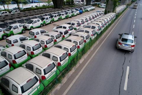 New electric vehicles parked in a parking lot under a viaduct in Wuhan, central China's Hubei province. STR/AFP/Getty Images