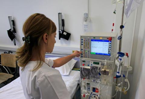 Una enfermera prepara una máquina de diálisis.
