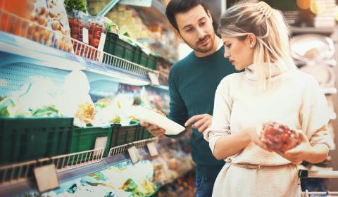 Pareja comprando frutas y verduras envasadas en el supermercado.