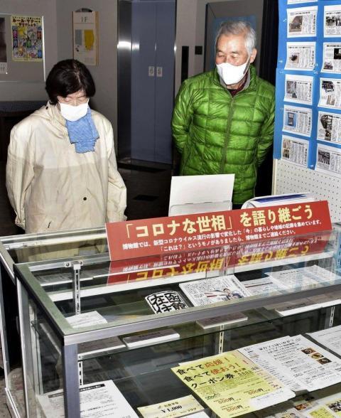 La gente mira los documentos relacionados con COVID-19 que se exhiben en el Museo Histórico de Urahoro