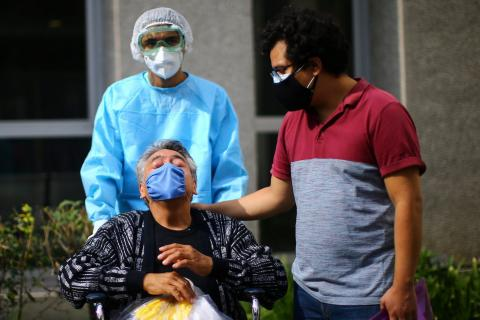 Rufino, a patient who has recovered from the coronavirus disease (COVID-19), gestures next to his son as he leaves from the Juarez Hospital to go to his house in Mexico City, Mexico, July 27, 2020. Edgard Garrido/Reuters