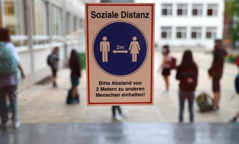 Una señal recuerda el distanciamiento social en un colegio de Alemania