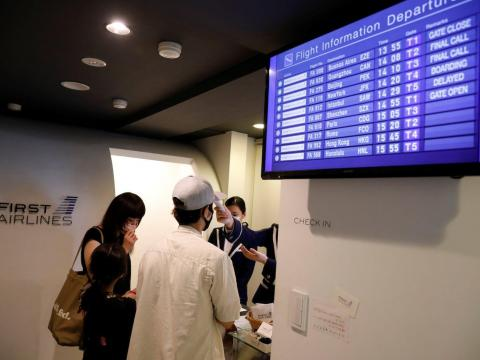 A staff dressed as a flight attendant checks temperature of a customer at a check-in desk at First Airlines in Tokyo, Japan, on August 12, 2020. Kim Kyung-Hoon/Reuters