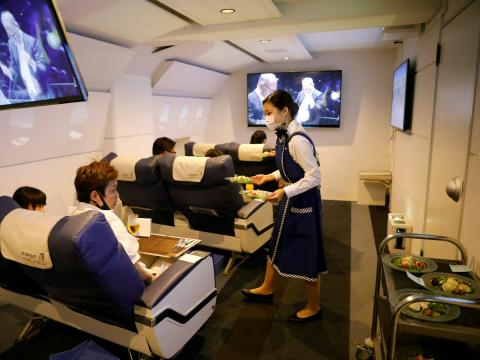 A staff dressed as a flight attendant serves meals to customers at First Airlines in Tokyo, Japan on August 12, 2020. Kim Kyung-Hoon/Reuters
