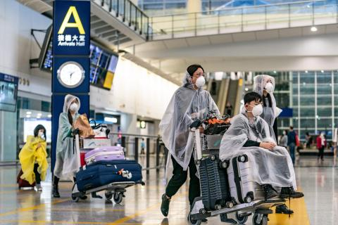 Travelers wearing protective equipment as a precautionary measure against COVID-19 enter the arrivals hall at Hong Kong International Airport on March 17, 2020 in Hong Kong, China. Anthony Kwan/Getty Images