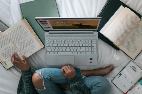 Estudiante con un portátil en la cama