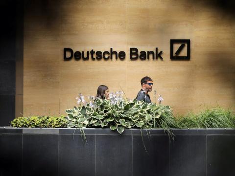 FILE PHOTO: People walk past a Deutsche Bank office in London. Reuters