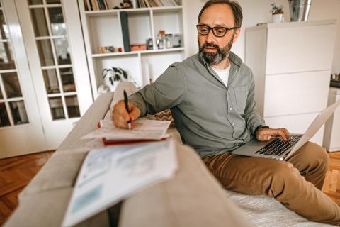 Hombre escribe en papel y ordenador documentos.