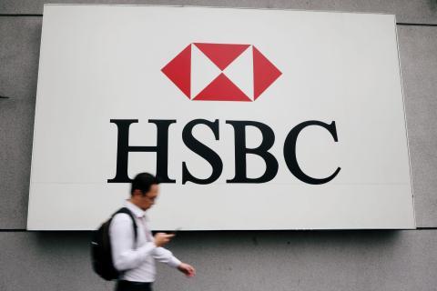 A man walks past a logo of HSBC at its headquarters in Kuala Lumpur. Reuters