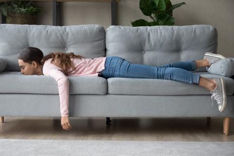 Una mujer acostada en el sofá con apatía.