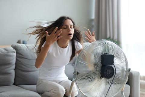 Mujer con calor con un ventilador.