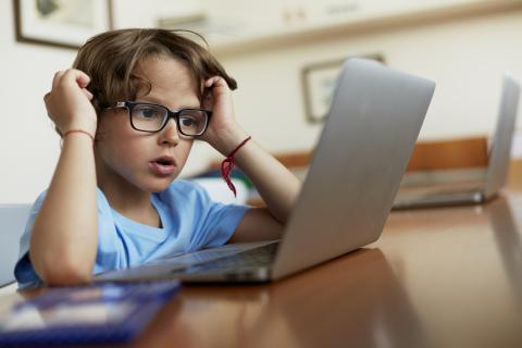 Niño con gafas en el ordenador.