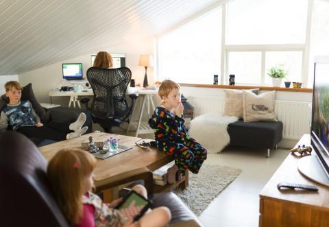 Niños viendo la tele mientras adulto trabaja