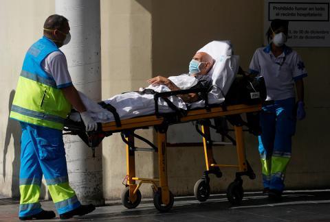 Sanitarios trasladan a un enfermo en una camilla al hospital 12 de Octubre de Madrid.
