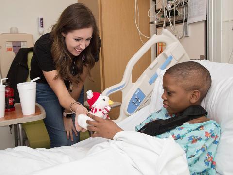 La cantante Francesca Battistelli (izquierda) visita a pacientes en el Aflac Cancer and Blood Disorders Center of Children's Healthcare de Atlanta.