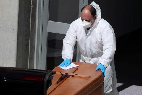 Un trabajador funerario con traje protector saca un ataúd de la morgue del Hospital Severo Ochoa.