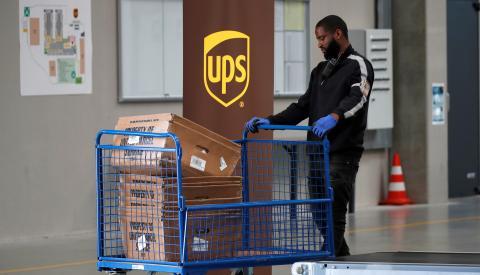Un trabajador de UPS transporta paquetes en un almacén de la compañía