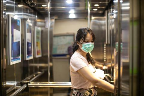 A young woman in an elevator wears a face mask to prevent coronavirus spread. Getty Images