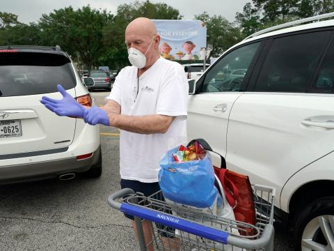 Gary Towler puts on gloves to protect against coronavirus, before entering a grocery store Wednesday, April 22, 2020, in Spring, Texas.
