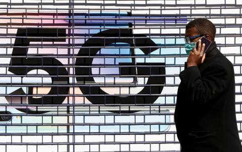 Un hombre camina delante de un cartel de 5G.