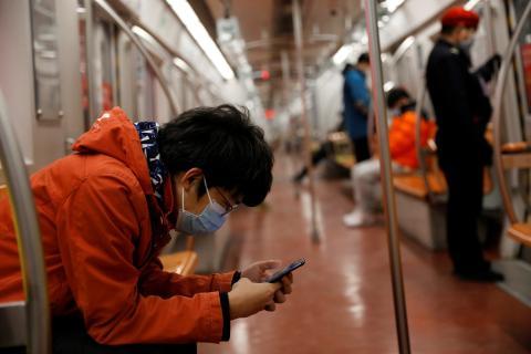Un hombre consulta su móvil en el metro de Pekín (China)