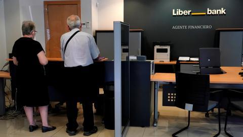 Una pareja de ancianos es atendida en la ventanilla de una sucursal de Liberbank en Madrid