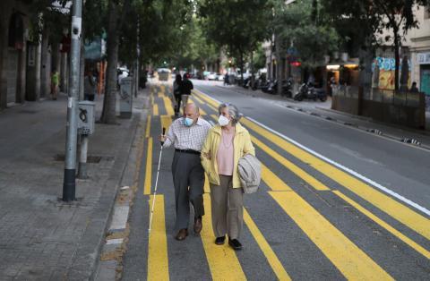 Una pareja de ancianos pasea con mascarilla