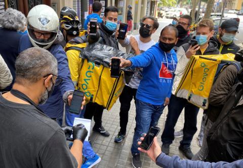 Repartidores de Glovo en un establecimiento de Barcelona recogiendo pedidos