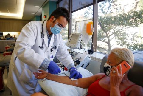 Un sanitario extrae sangre de una paciente recuperada de COVID-19 para donar plasma convaleciente.