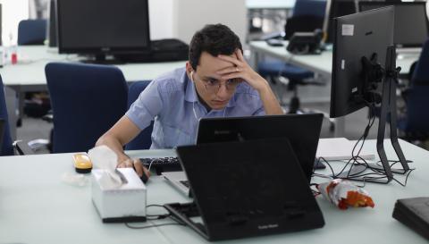 Un trabajador de un fondo de inversión iraní sigue la cotizacion de las bolsas desde su ordenador