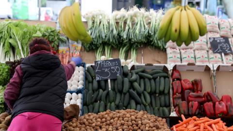 Una verdulera coloca las frutas de su puesto en un mercado de Madrid