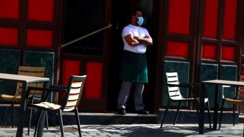 Un camarero con mascarilla a las puertas de un bar de España