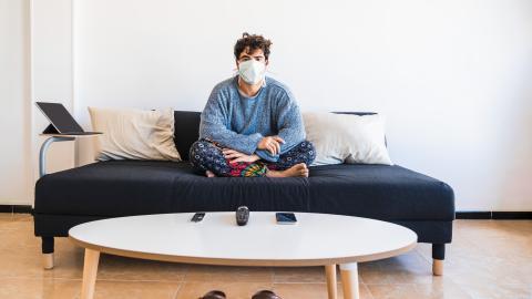 Un chico con mascarilla en casa.