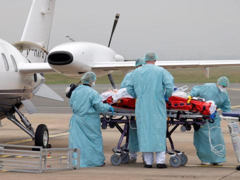 Miembros del personal médico trasladan a un paciente que padece el coronavirus a un avión durante una operación de traslado desde el aeropuerto de Lille-Lesquin, en Francia, al aeropuerto de Munster, en Alemania, el 10 de noviembre de 2020.