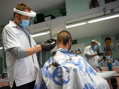 Un peluquero con mascarilla y pantalla protectora mientras corta el pelo.