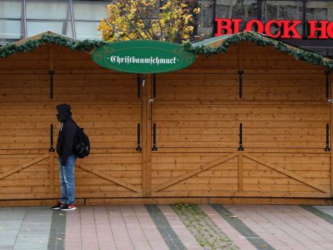 Un hombre está de pie frente a un puesto de adornos de árbol de Navidad cerrado en el cancelado mercado anual de Navidad durante la segunda ola de la pandemia de coronavirus el 12 de noviembre de 2020 en Essen, Alemania.