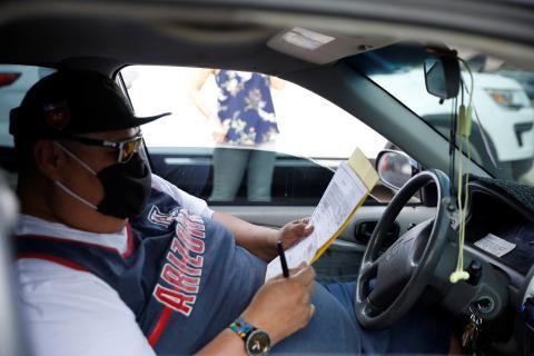 Un hombre decide su voto sentado en el coche.
