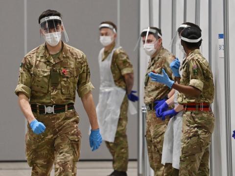 Soldados con EPP completo esperan en un centro de pruebas rápidas de coronavirus en Liverpool, Inglaterra, el 11 de noviembre de 2020.