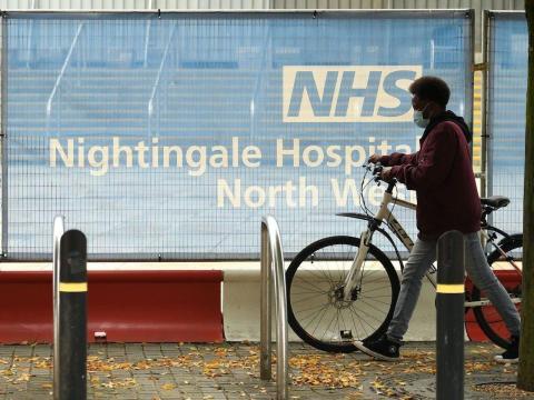 Un ciclista con mascarilla empuja una bicicleta a través de una barrera en las afueras del hospital de campo NHS Nightingale Hospital North West, establecido para proporcionar más capacidad hospitalaria durante la pandemia, el 13 de octubre de 2020.