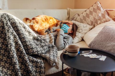 Mujer con mascarilla en el sofá con su gato.