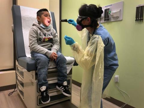 Un niño es examinado por un asistente médico antes de recibir una prueba de hisopo COVID-19 el 5 de mayo en Stamford, Connecticut.